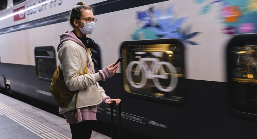 Girl with COVID mask getting on a train